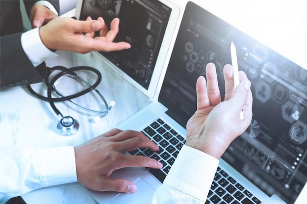 医療技術ネットワークチーム会議のコンセプトです。医師の手を働くスマートフォン現代デジタルタブレットラップトップコンピューターグラフィックスチャートインターフェイス、太陽フレア効果写真