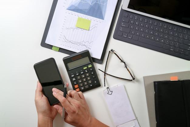 近代的なオフィスの机の上の携帯電話でコストと電卓とラップトップについての財政で働くビジネスマン手のトップビュー