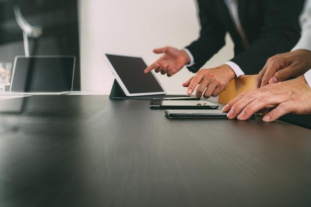 共同作業チーム会議のコンセプト、近代的なオフィスにスマートフォンとデジタルタブレットとラップトップコンピューターを使用しての実業家