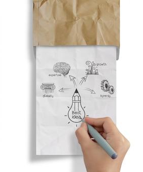 手は、リサイクルの封筒から電球のしわくちゃの紙を描画します