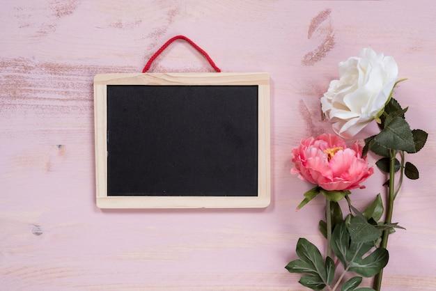 ピンクの背景に花がある黒板
