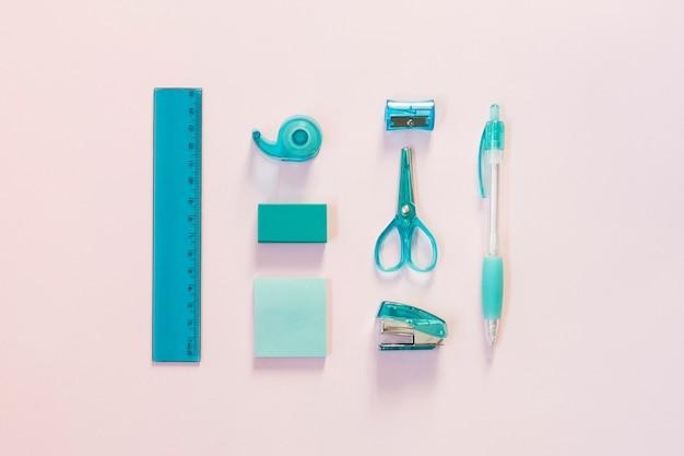 ライトピンクの背景に青色の学校用品