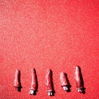 赤いキラキラの背景の上に偽の怖い指