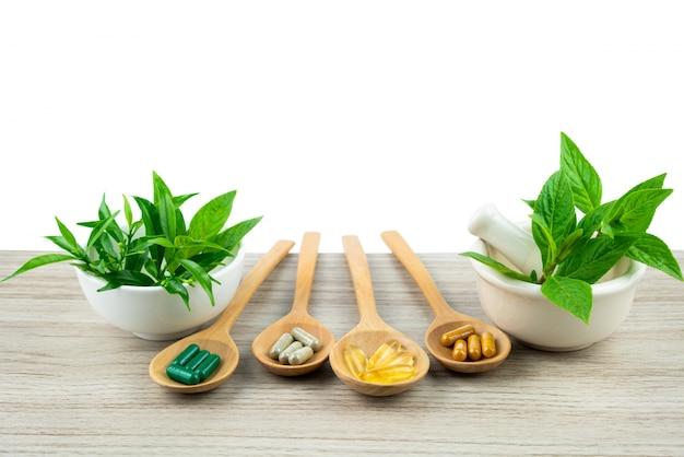 医療の背景のコピースペースを持つ木製のテーブルの上のカプセルの漢方薬