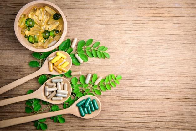 木のスプーン、有機漢方薬、木製の背景の補足の酸化防止剤ビタミンカプセル