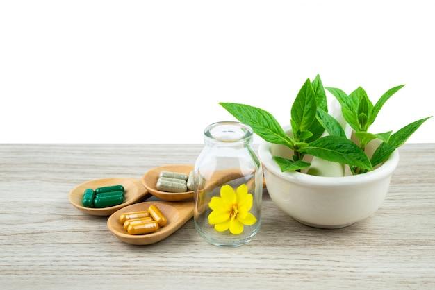健康のためにハーブの性質からハーブカプセル、木製のテーブルにサプリメントの丸薬