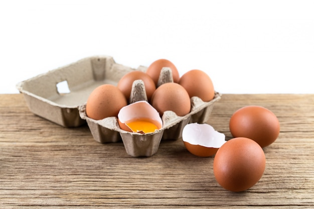 素朴な木製のテーブルの自然からの有機食品、卵箱で生の鶏の卵のクローズアップ