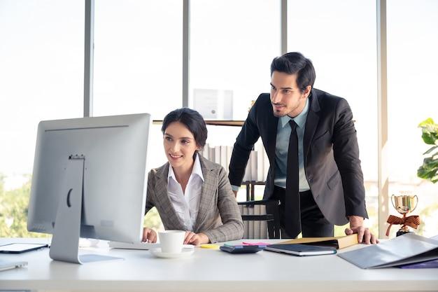 ビジネスの男性と女性のオフィスでラップトップを探していると成功のために幸せ