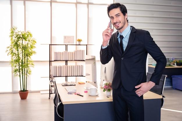 ビジネスコミュニケーション。オフィスで立っている電話で話している実業家