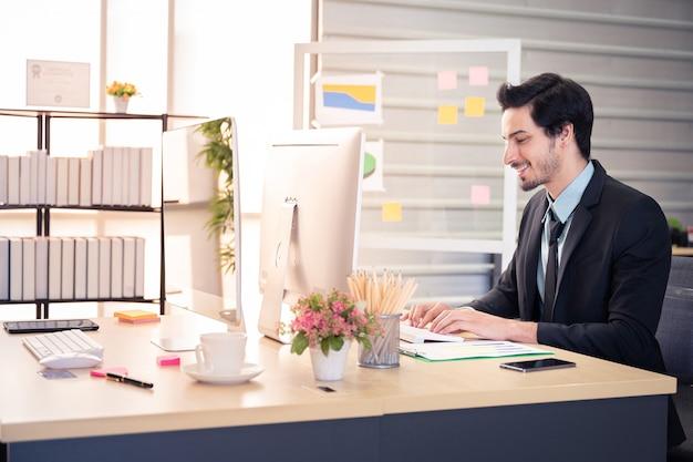 幸せの実業家とオフィスのコンピューターでの作業中に笑顔