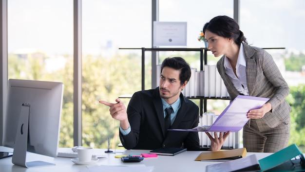 ビジネスマンおよび女性探しているとオフィスでラップトップを指す