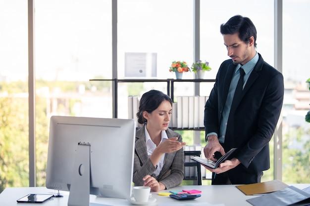 ビジネスマンおよびオフィスでラップトップを探している女性と成功のために幸せ