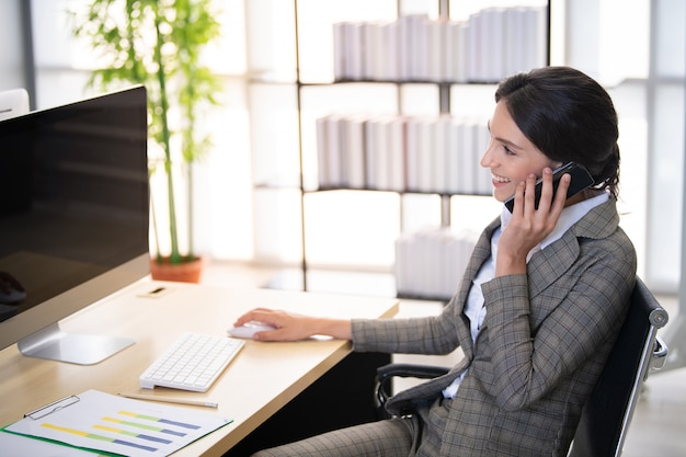 オフィスでのコミュニケーションのための電話のビジネス女性