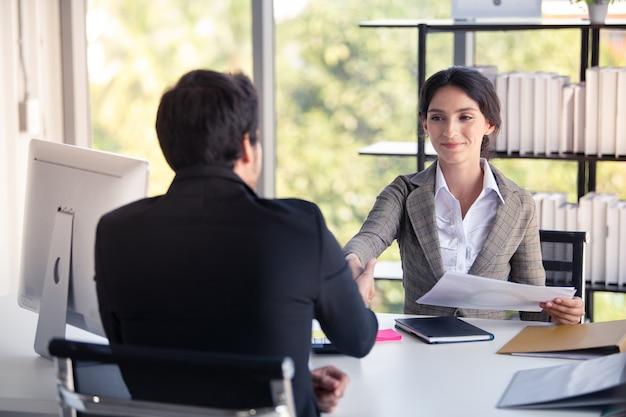 ビジネスマンおよび女性のオフィスで握手と成功のために幸せ