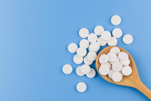 医学、丸薬、薬の錠剤、カプセル、魚油、スプーンで青の背景に分離