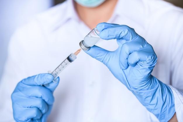 Врач, исследователь, ученый рука держит бутылку вакцины против гриппа, кори, полиомиелита, краснухи или впч