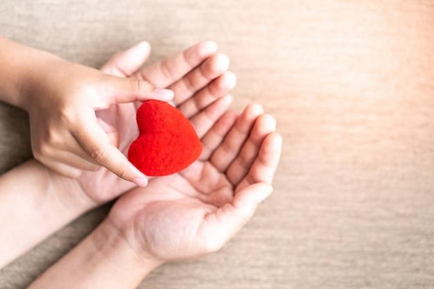 Ребенок дает красное сердце матери