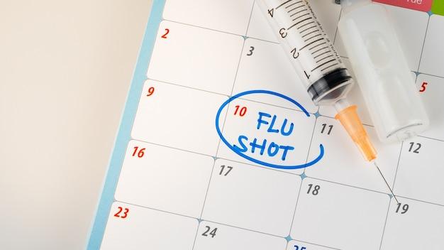 医師リマインダーインフルエンザ注射器、薬、ワクチンの概念とカレンダーで撮影
