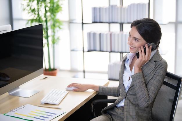 近代的なオフィスに電話でビジネスの女性。