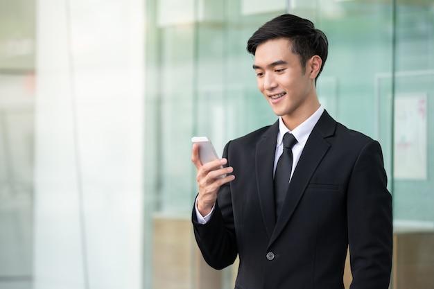 仕事やオンラインショッピングに携帯電話を使用してビジネスの男性。