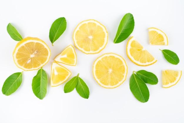 Свежий ломтик лимона с листьями на белой стене