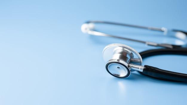 Черный стетоскоп, медицинский инструмент для здравоохранения на синей стене с копией пространства