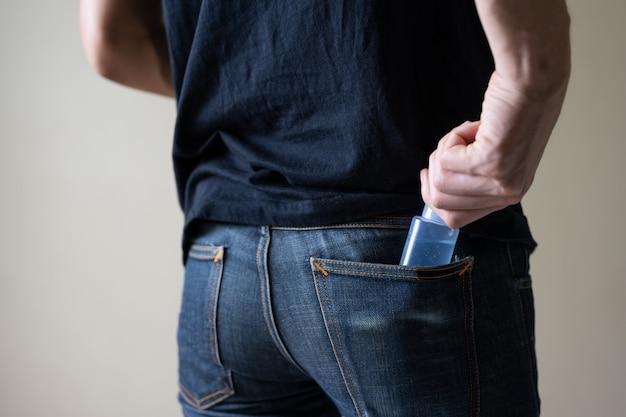 Человек несет дезинфицирующее средство для рук гель-флакон в карман джинсов для профилактики коронавируса