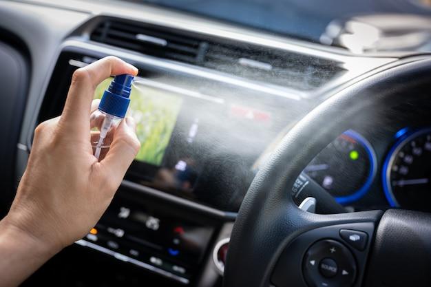 Человек распыляя спирт для чистой поверхности в автомобиле