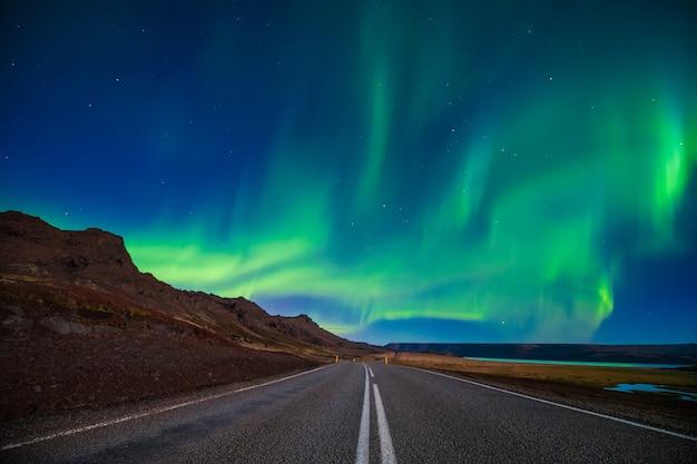空の道と秋、アイスランドの山の上のオーロラ