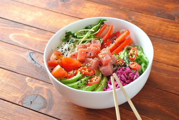 自然食品。新鮮なシーフードのレシピ。クリスタルヌードル、新鮮なキャベツ、アボカド、チェリートマトのマグロポークボウル。木製の背景に食品コンセプトポークボウル