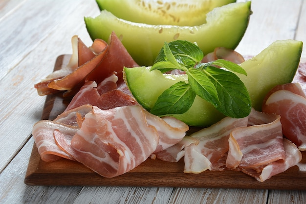 Салями, прошутто, бекон с дыней и мятой на разделочной доске. итальянский обед