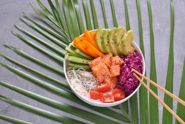Рецепт свежих морепродуктов. органическая еда. тушеная свежая семга с хрустящей лапшой, свежей красной капустой, авокадо, помидорами черри. продовольственная концепция тыкать миску
