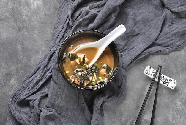 新鮮なマグロ、乾燥海苔、豆腐、しいたけ、木製の背景に木製のボウルに日本の茸の味噌汁