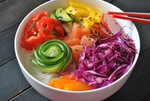 Выложить миску со свежим лососем, хрустальной лапшой, редисом, авокадо, сладким перцем, огурцом, кунжутом, красной капустой. органическая еда. рецепт свежих морепродуктов. продовольственная концепция тыкать миску на деревянных фоне