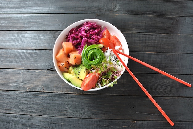 Органическая еда. рецепт свежих морепродуктов. свежий лосось тыкать шар с рисом, свежей красной капустой, авокадо, помидоры черри, огурец, ростки редиса на деревянных фоне. продовольственная концепция тыкать миску