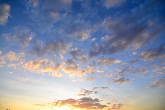 青い空、暖かい色の日の出、スカイラインの上の太陽の上の雲と美しいオレンジ色の夕日