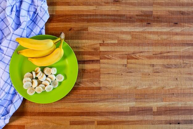 Банановая гроздь и ломтики на зеленой тарелке на натуральном деревянном столе