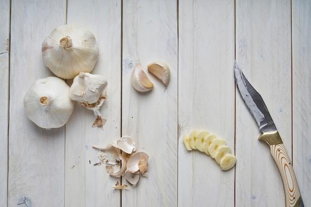 いくつかの頭、いくつかのクローブ、白い木製のテーブルにニンニクのスライスの静物