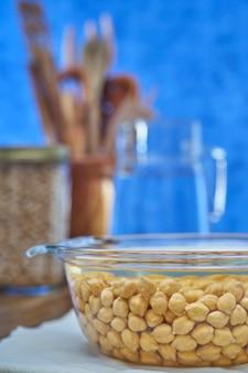 ひよこ豆は青い背景で調理するための水のボウルに浸した。