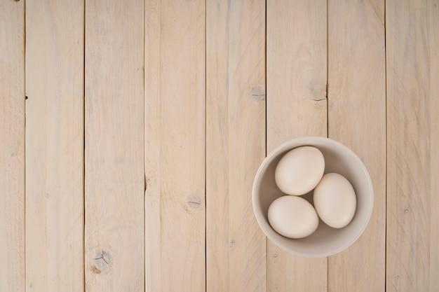 木製の背景上にボウルに鶏の卵のグループ