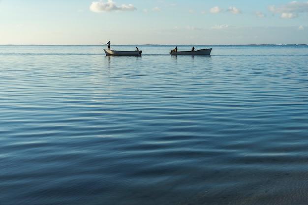穏やかな海と夜明けに交差する漁船