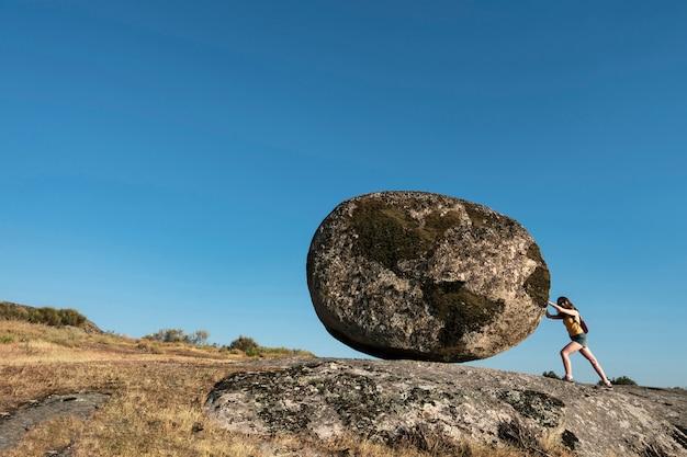 世界の岩を押す女性。