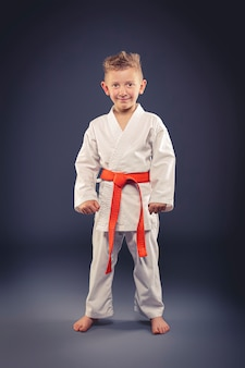 Портрет улыбающегося ребенка с кимоно практикующих боевые искусства