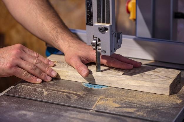 Деталь руки плотника рядом с лезвием ленточной пилы.