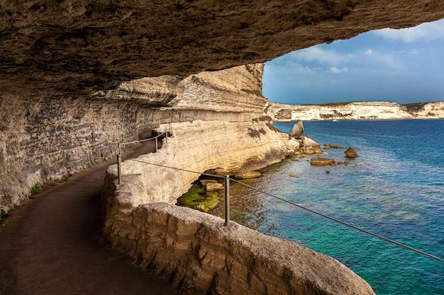 Живописная тропа высечена в скале, которая проходит вдоль моря в городе бастия на корсике