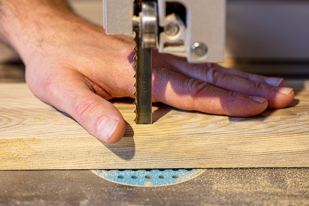 Деталь на руке плотника неправильно и опасно размещена рядом с полотном ленточной пилы.