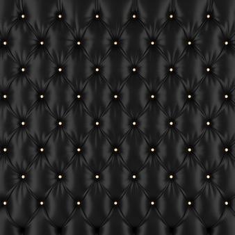 Текстурная деталь стеганого черного кожаного дивана с золотистыми пуговицами.