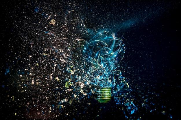 Взрыв стеклянной колбы на черном фоне. скоростная фотография.