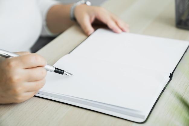Сочинительство руки женщины на пустой тетради на таблице в доме.