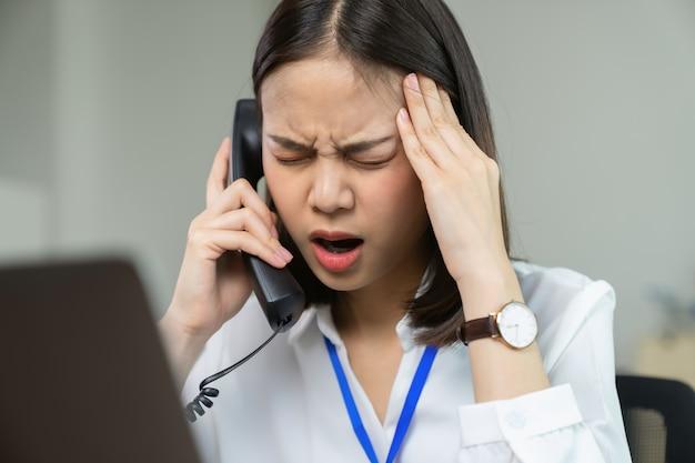 電話で話しているアジアの女性は、長い間仕事と緊張のために頭痛を抱えています。オフィス症候群。